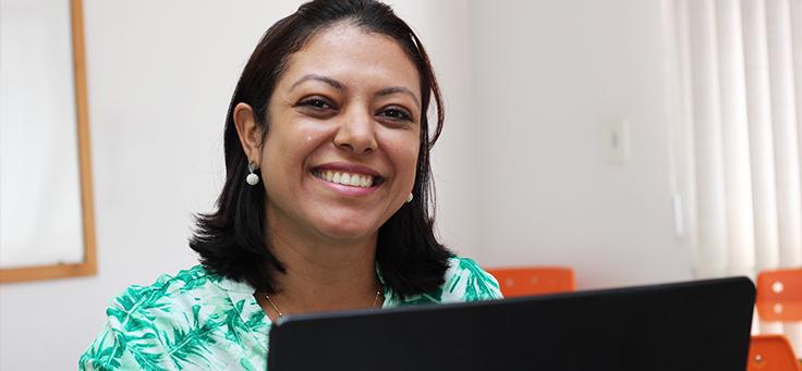 Imagem é um retrato da professora Maisa Nunes, que uniu em projeto leitura, tecnologia e pesquisa. Ela tem cabelos na altura dos ombros, está sorrindo e usando um computador.