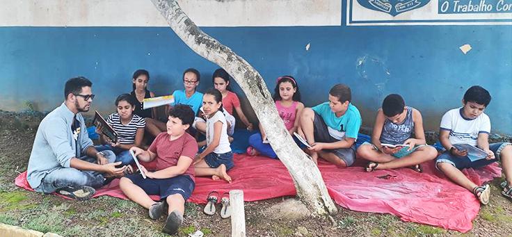 Na imagem professor Isaias Silva está sentado embaixo de uma árvora com grupo de alunos em projeto que alia leitura, tecnologia e pesquisa