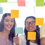 Imagem ilustra a Semana Global do Empreendedorismo e mostra grupo de quatro jovens olhando para post its colados em uma parede transparente