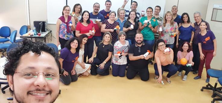 Grupo com homens e mulheres posa em sala de aula, segurando material de formação da Assessoria Inova Escola, que promove inovação educativa na rede pública, em Goiás.