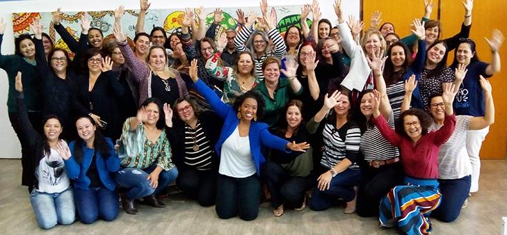 Professoras posam com os braços para cima em celebração após formação continuada da Fundação Telefônica Vivo em parceria com a Undime.