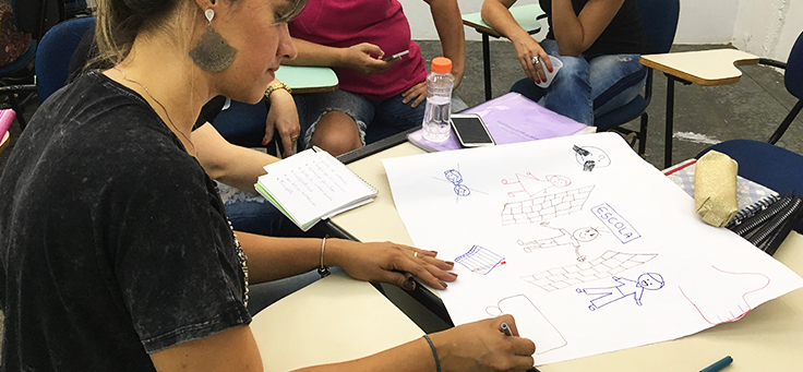 Professora está desenhando em cartolina durante dinâmica de formação continuada da Fundação Telefônica Vivo em parceria com a Undime.