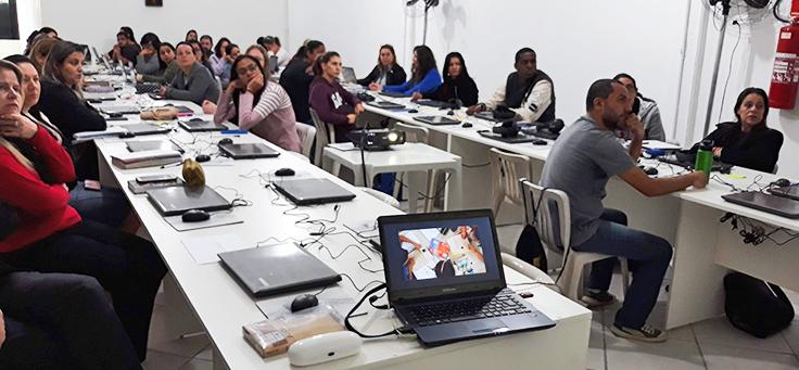 Professores estão sentados em frente a computadores, assistindo a projeção durante formação continuada da Fundação Telefônica Vivo em parceria com a Undime.