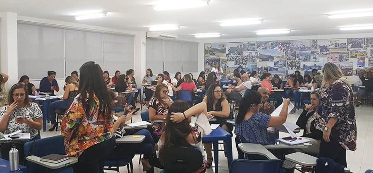 Professores estão sentados em grupos durante formação continuada da Fundação Telefônica Vivo em parceria com a Undime.