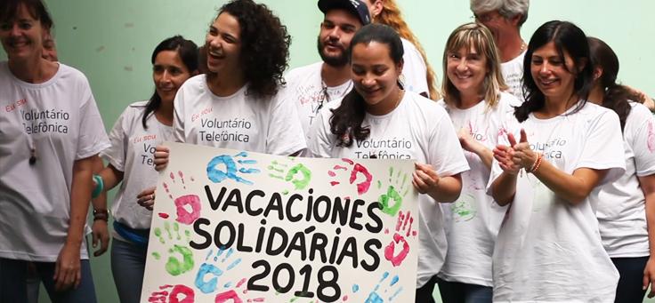 Na imagem, colaboradores vestindo a camiseta do programa Vacaciones Solidárias seguram cartaz ilustrado com carimbo das mãos de jovens da Escola Especializada Primavera.