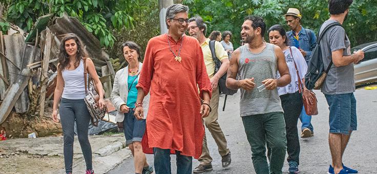 Manish Jain anda pelo Jardim Ângela em São Paulo. Ele está usando uma bata laranja e está rodeado por jovens do bairro.