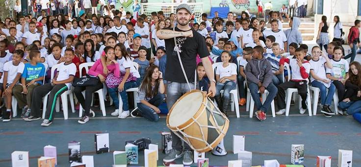 O professor Rodrigo Ciríaco, criador do Sarau dos Mesquiteiros ao lado de alunos, segura um tambor. Ao fundo é possível ver uma plateia formada por jovens