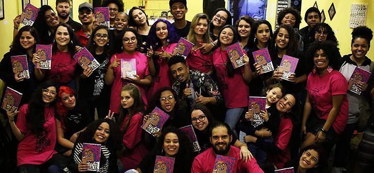 Grupo de jovens está segurando livro de coletânea publicado pelo selo do projeto do Sarau dos Mesquiteiros.