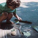 Menino está agachado olhando para gravetos e folhas contornados por giz no asfalto – conheça projetos que usam o lúdico no aprendizado.