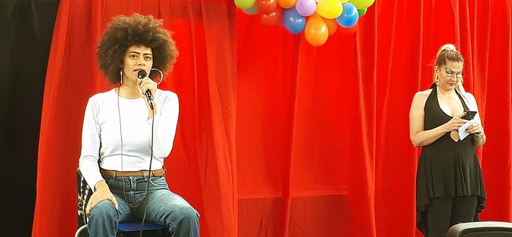 Duas mulheres ocupam um palco durante o Brito sem homofobia. Uma delas usa cabelo cacheado em estilo black power.