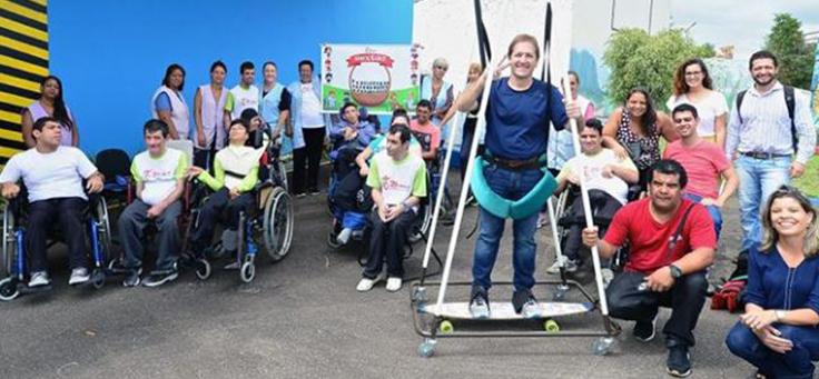Sidney Barboza, que atua em causas sociais, está em cima de um skate adaptado a pessoas com deficiências durante ação voluntária.