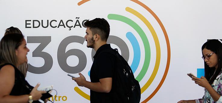 Na imagem, vemos jovens circulando em frente ao longo do evento Educação 360, composto de linhas circulares coloridas.
