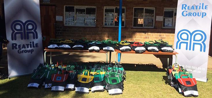 Na imagem, dezenas de bolsas com bateria acopladas e que auxiliam a educação de crianças estão agrupadas no chão e sobre duas mesas, em cima de um gramado.