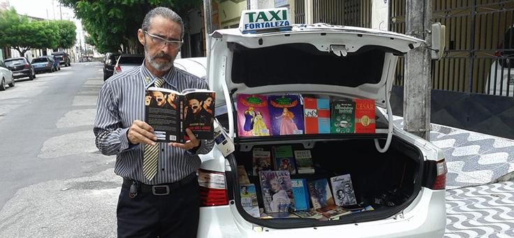 Motorista conhecido como Carlos Careca está com um livro na mão posando em frente ao táxi que dirige – matéria sobre o bibliotaxi foi destaque em empreendedorismo social em 2018.