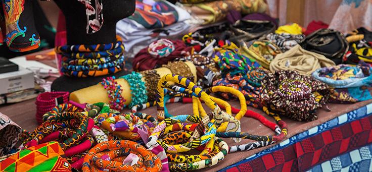 Itens como pulseias e colares coloridos estão dispostos em uma bancada – matéria sobre a Feira Preta foi destaque em empreendedorismo social em 2018.