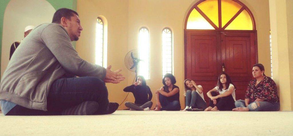 Homem conversando com cinco jovens, todos estão sentados no chão de uma igreja – matéria sobre combate à intolerância religiosa foi destaque em Voluntariado em 2018.
