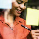 Imagem mostra uma jovem sorrindo enquanto escreve em um post it – matéria relembra os destaques em empreendedorismo social no site da Fundação Telefônica Vivo em 2018
