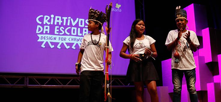 Três alunos, usando cocar e arco e flecha, estão no palco do prêmio Criativos da Escola, onde o dicionário das línguas ofaié e guarani ganhou prêmio ao resgatar culturas marginalizadas.