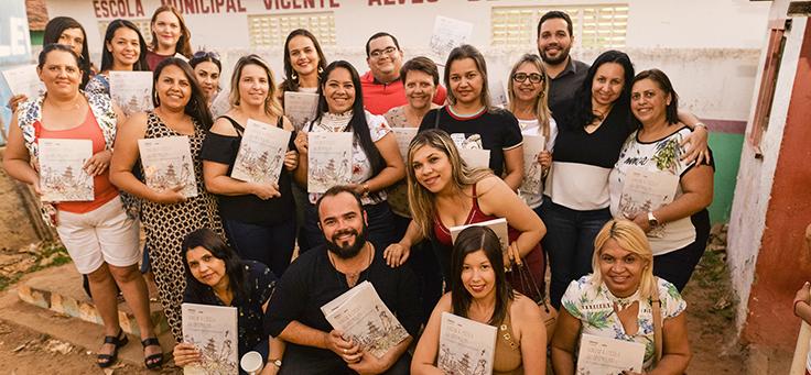 Educadores e formadores responsáveis pelo caderno que reúne boas práticas educacionais de Saloá-PE seguram a publicação e posam agrupados para a foto.