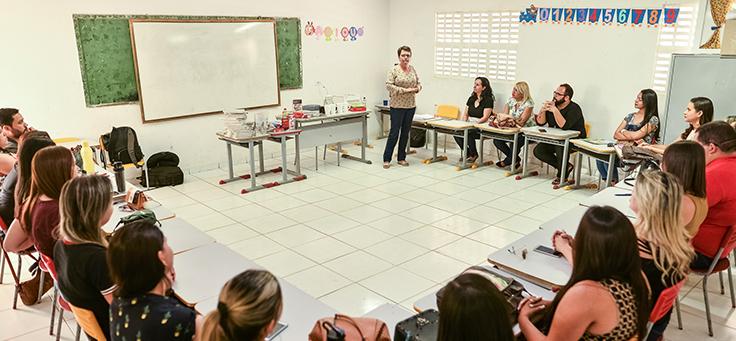 Professores estão sentados em cadeiras dispostas em formato de roda durante formação que originou a publicação do caderno que reúne as boas práticas educacionais de Saloá-PE.