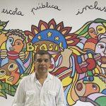 Diretor da Escola Infante Dom Henrique, que recebe refugiados, posa para foto com um painel ao fundo