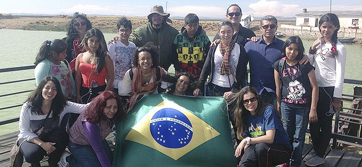 Um grupo de brasileiros e estrangeiros posa para a foto com a bandeira do Brasil. Matéria debate inclusão de refugiados