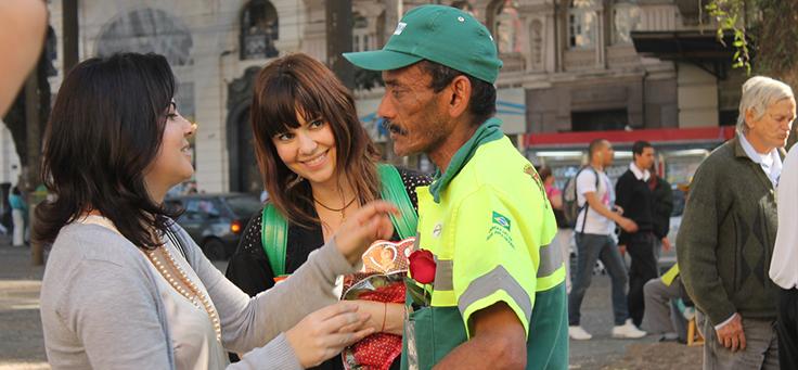 Imagem mostra Renata Quintella e outra voluntária conversando com um gari nas ruas de São Paulo