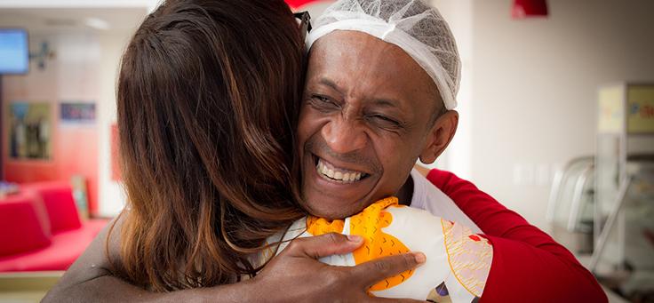 Imagem mostra Renata Quintella abraçando um homem de touca.