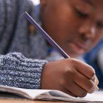 Na imagem criança escreve com lápis vermelho para ilustrar entrevista com a educadora Mara Mansani, sobre a alfabetização no século XXI.