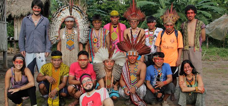Equipe do antropólogo e game designer Guilherme Pinho Meses posa em meio a representantes do povo Kaxinawá, trajando cocar e pinturas com jenipapo e urucum