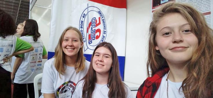 As alunas Manoela Kieling, Laura Schuster e Julia Dapper, que ajudaram a desenvolver o aplicativo de combate ao bullying, estão sorrindo para a foto com uma bandeira da Escola Municipal de Ensino Fundamental 25 de Julho ao fundo.