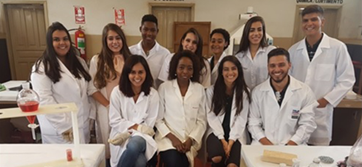 Alunos da professora Joana, posam para foto em grupo, vestidos de jaleco dentro do laboratório.