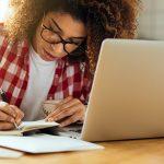 Jovem de cabelos cacheados usando óculos está escrevendo em um papel apoiado em uma mesa, em frente a um notebook. Imagem ilustra matéria sobre cursos gratuitos do Escolas Conectadas.