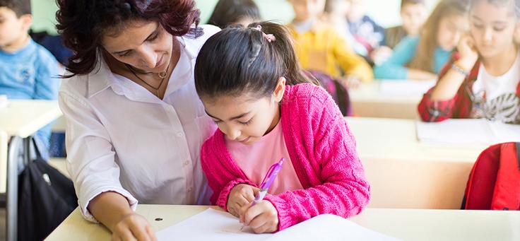 Mulher está sentada ao lado de menina, que está escrevendo. Imagem ilustra matéria sobre educação inclusiva