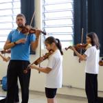 O professor de violino Ezequiel Sieba está em sala de aula com os alunos tocando violino