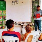 O professor José Gilson Lopes, que desenvolveu o projeto Mala de Leitura para incentivar a inclusão por meio do hábito de ler, está em pé em frente a alunos, mostrando uma mesa cheia de livros.