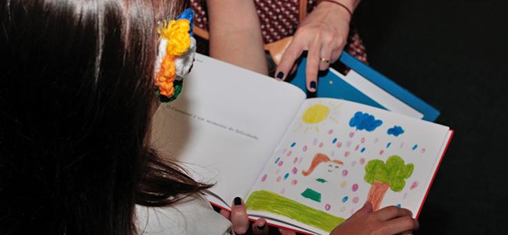 Criança está lendo página desenhada de livro publicado pelo Estante Mágica, projeto que publica histórias escritas por crianças.