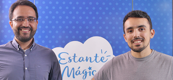 Robson Melo, de camisa e óculos, está ao lado de Pedro Concy, usando barba e camiseta. Eles são criadores do Estante Mágica, projeto que publica histórias escritas por crianças.