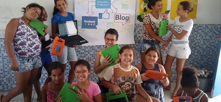 Grupo de alunos da Escola Municipal Manoel Domingos está segurando tablets e notebooks para atividades com redes sociais, que pautou discussão sobre internet segura.