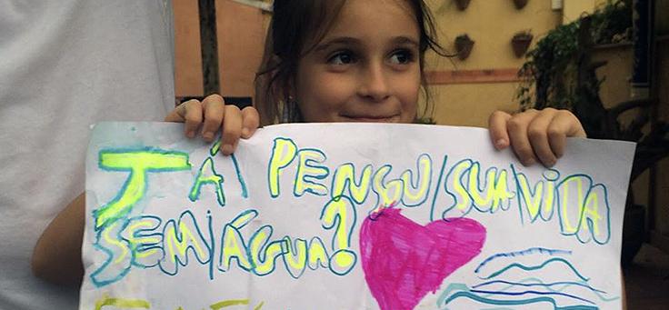 """Na imagem, uma menina segura um cartaz com os dizeres """"Já pensou sua vida sem água?""""."""