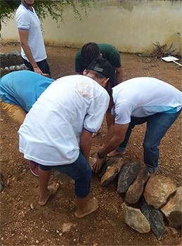 Imagem mostra estudantes arrumando cordão de pedras