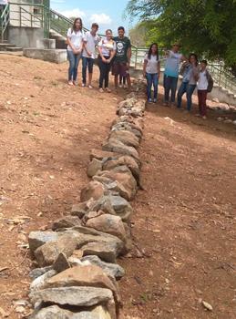 Imagem mostra pedras alinhadas em meio a área de revitalização da horta