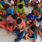 A imagem mostra crianças sentadas no chão com tablets nas mãos.