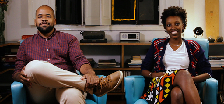 A imagem mostra dois jovens empreendedores sentados em poltronas azuis dentro de um estúdio de som