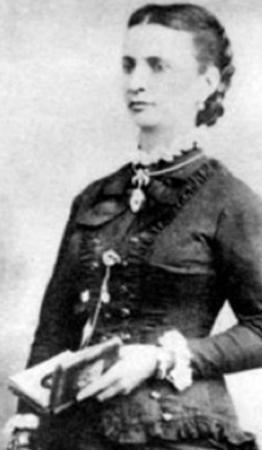 Nísia Floresta, uma das representantes de mulheres poderosas, está segurando um livro e usando vestido de época em um retrato em preto e branco.