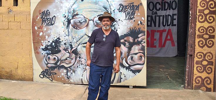 José Soró, arte-educador que atua no bairro de Perus, posa em frente a mural grafitado na sede da Comunidade Cultural Quilombaque.