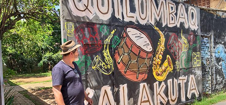 O arte-educador e gestor José Soró está olhando para o portão da sede da Comunidade Cultural Quilombaque em Perus, que tem instrumentos de sopro e um tambor desenhados.