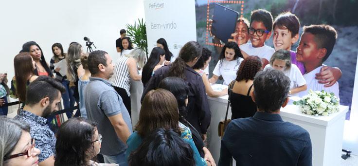 Imagem mostra grupo de pessoas em frente a uma mesa de credenciamento. Atrás da mesa há um banner onde se lê Profuturo – Bem-Vindo. Ao lado do texto há uma foto com quatro crianças abraçadas olhando para a tela de um tablet.