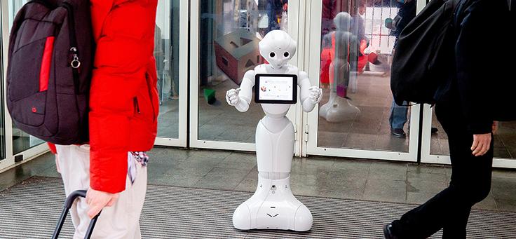 Imagem mostra um robô branco segurando um tablete em frente a uma porta de vidro