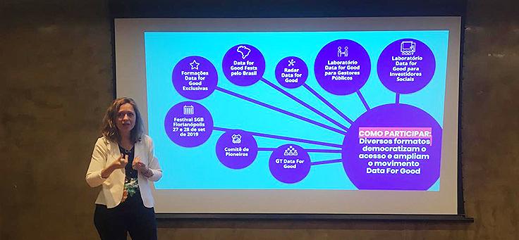 Carolina de Andrade, diretora-executiva do Social Good Brasil, está dando uma palestra no Data for Good, com um slide ao fundo.